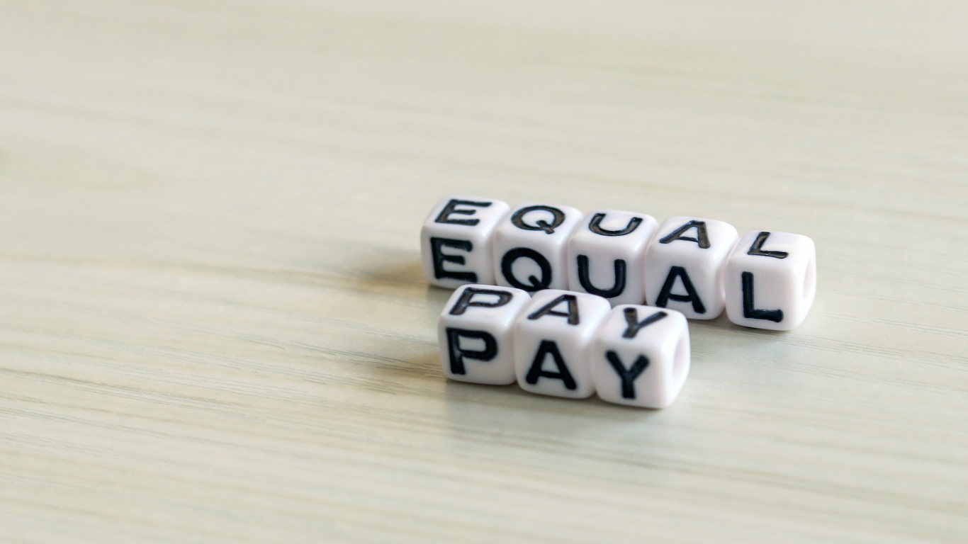 Equal pay text cube on the wood background.