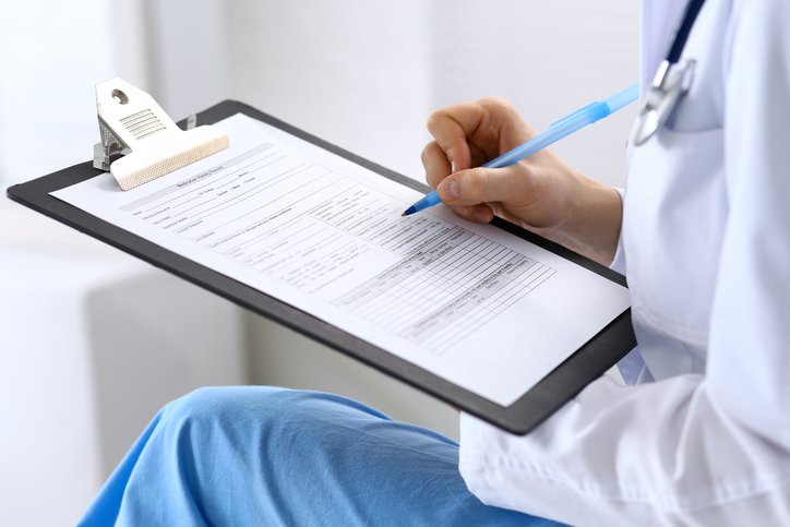 Female doctor filling up medical form on clipboard closeup.  Physician finishing up examining his patient in hospital and ready to give a prescription to help. Healthcare, insurance and medicine concep