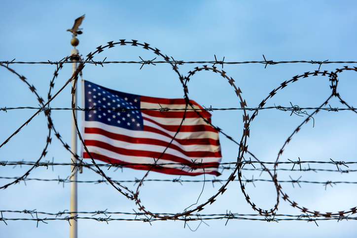Flag_behind_barbed_wire