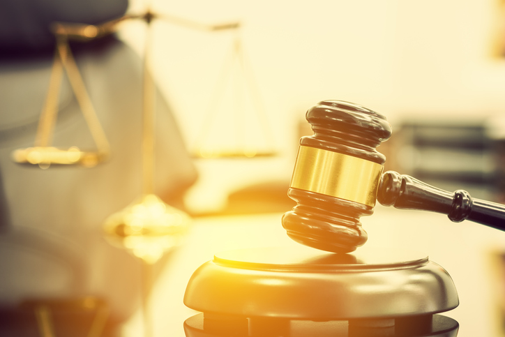 Legal office of lawyers, justice and law concept : Wooden judge gavel or a wood hammer and a soundboard used by a judge person on a desk in a courtroom with a blurred brass scale of justice behind.