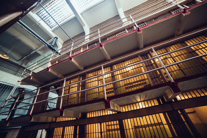 Prison cells in big jail and security guard.