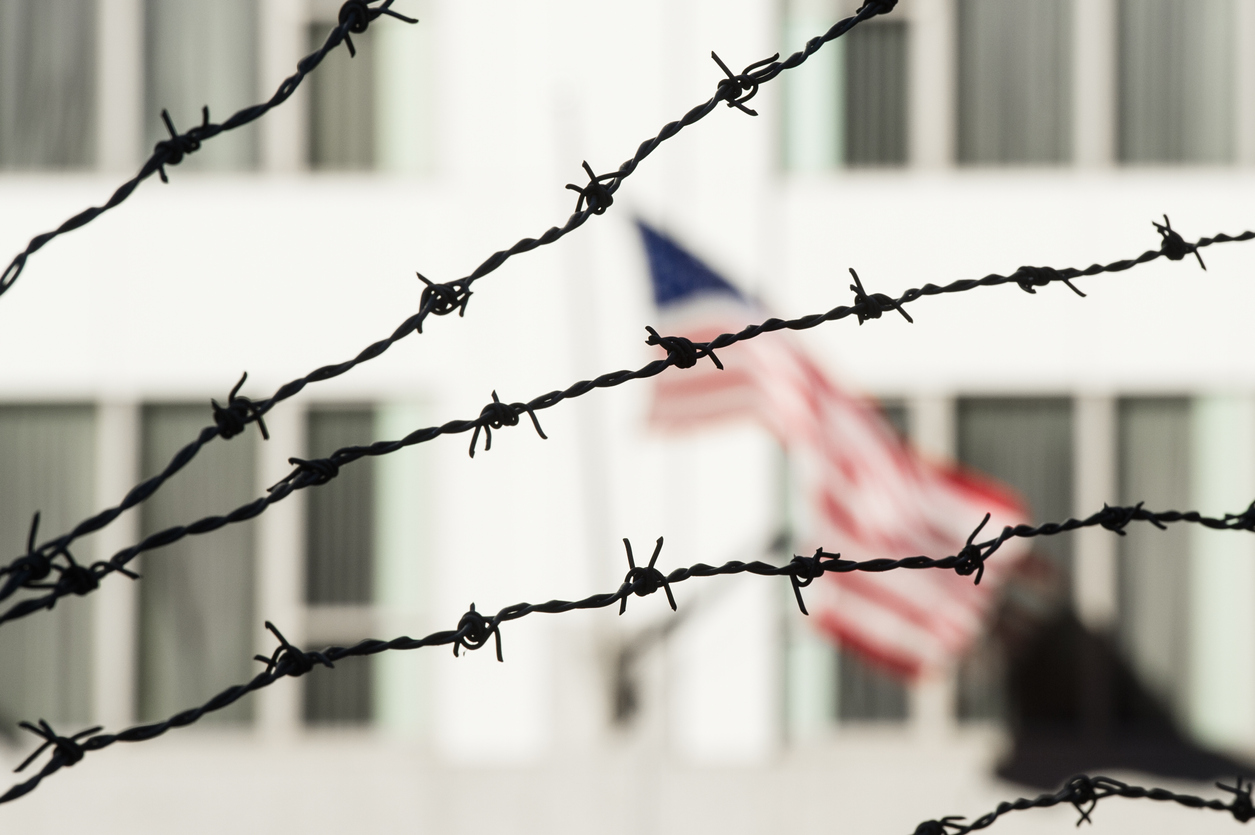 Barbed wire in the foreground and the blurred American flag in the background. Manhattan, New York city, USA.