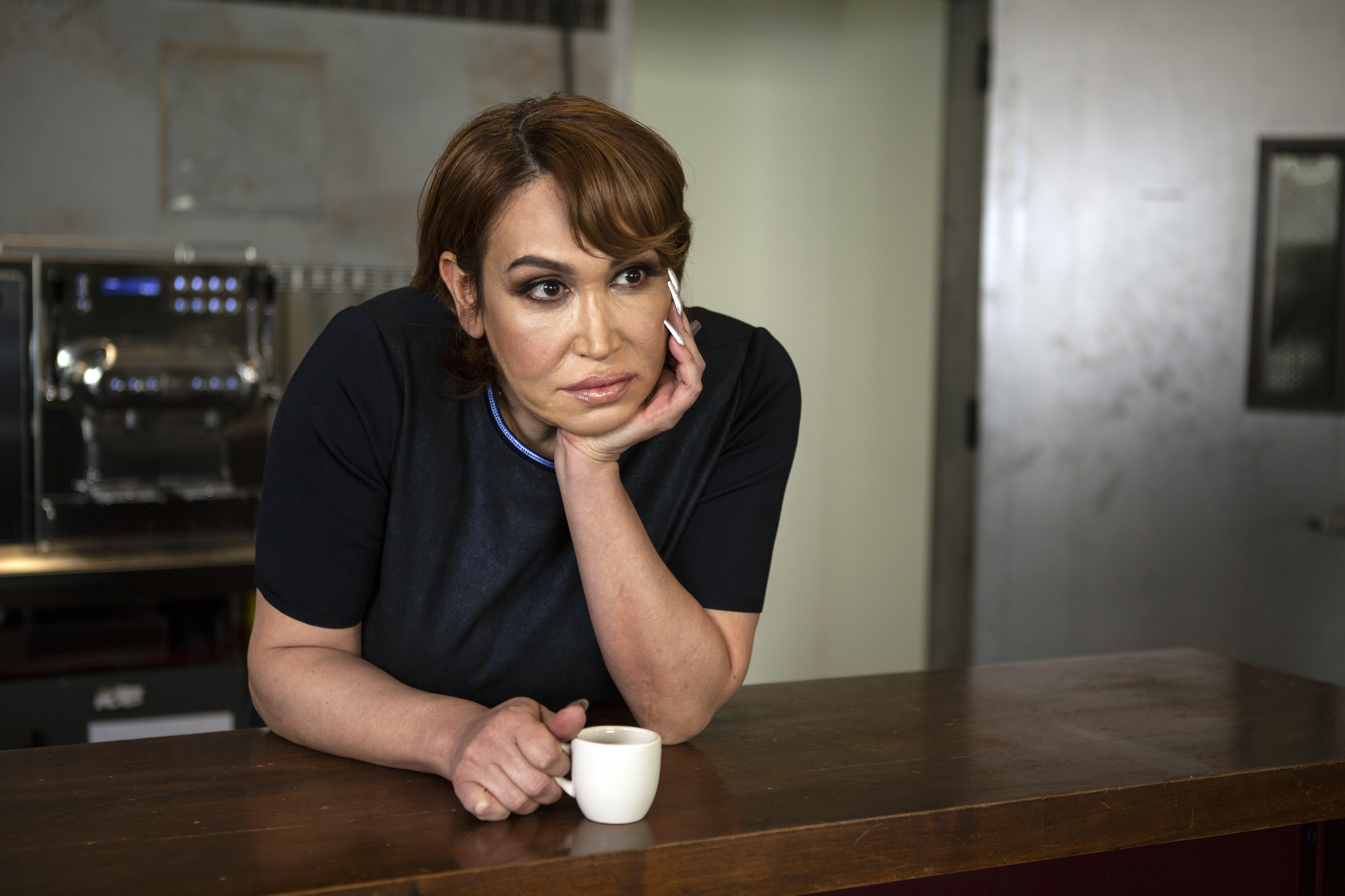 A transgender woman with an espresso standing at a bar and contemplating