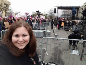 Marissa Ditkowsky, a white woman with dark, long hair, a black coat, and a walker, stands in front of a large crowd and a stage at the Women's March in January 2017. Marissa would like to recognize activist Mia Ives-Rublee for ensuring the Women's March was an accessible and inclusive experience for her and other disabled protestors.