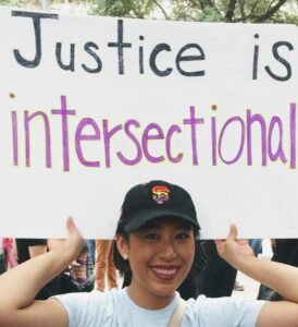 """Peggy Li is holding up a sign that says """"Justice is intersectional"""""""