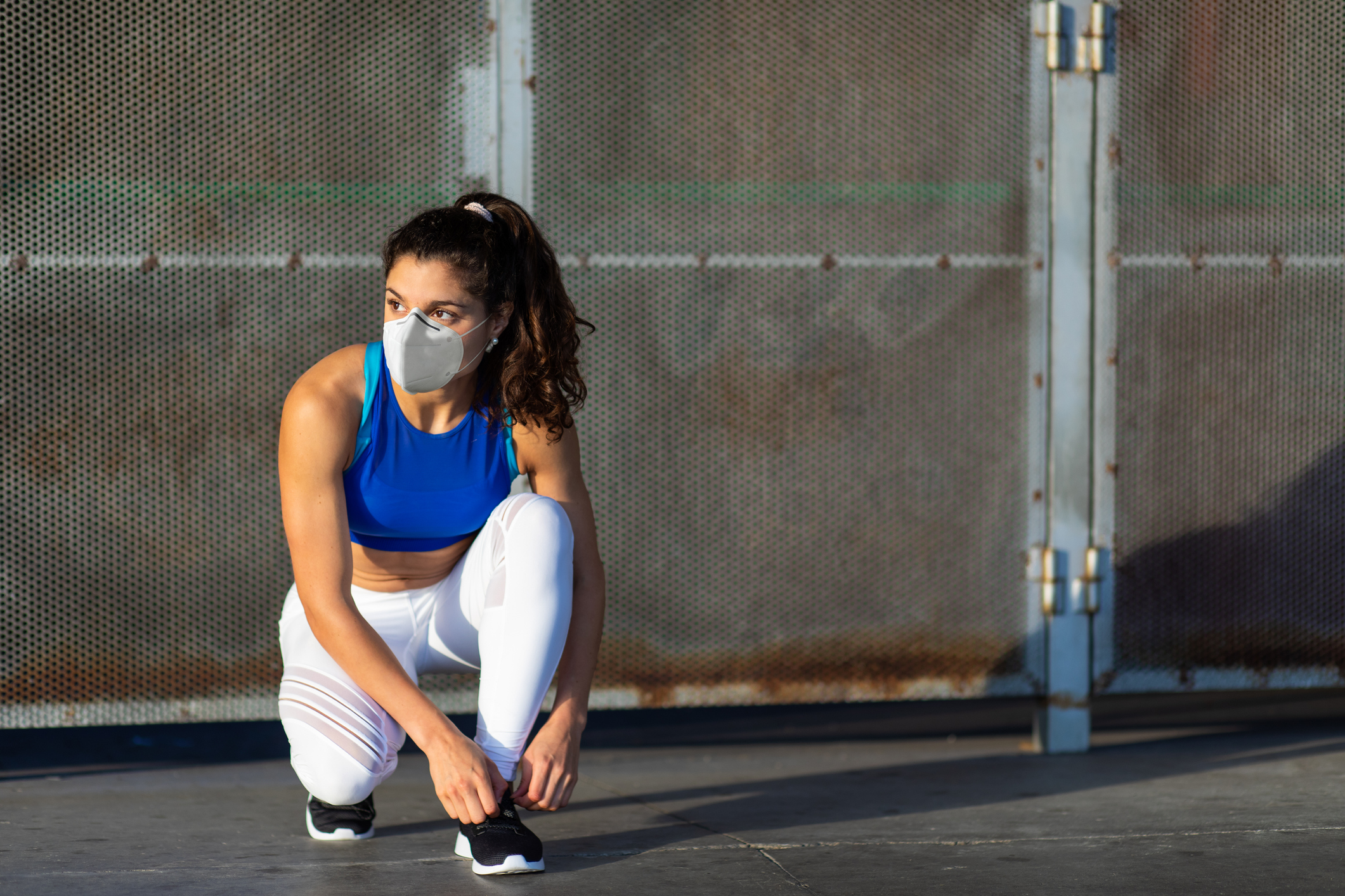 Young fit female athlete getting ready for running under coronavirus pandemic crisis