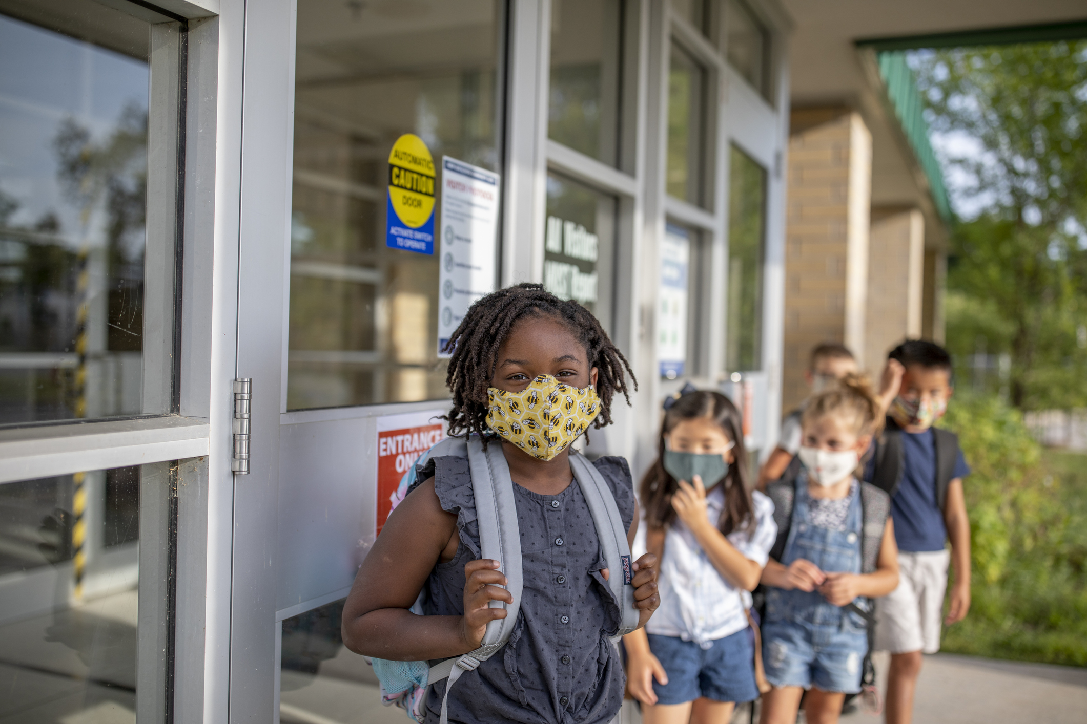 group of little kids in front of a school with backpacks and masks